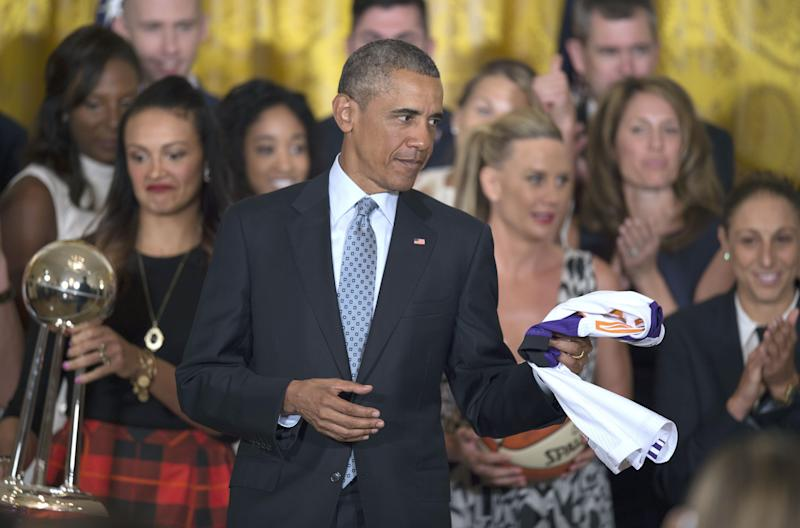 US President Barack Obama holds a jersey given to him during an event congratulating the 2014 WNBA champions Phoenix Mercury at the White House in Washington, DC, August 26, 2015. AFP PHOTO/JIM WATSON (Photo credit should read JIM WATSON/AFP/Getty Images)