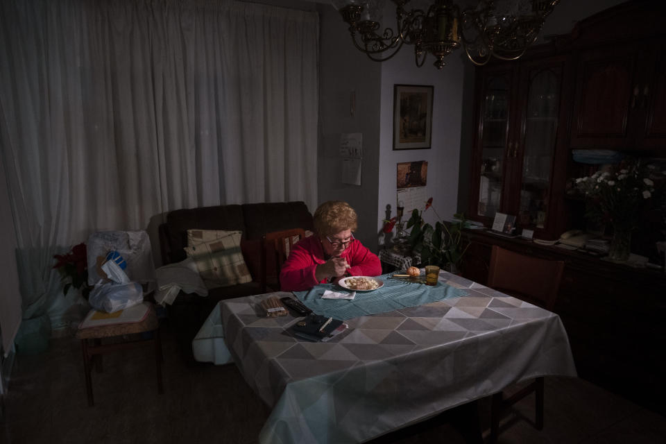 Rosa Otero, 83, eats her Christmas Eve dinner at her home in Barcelona, Spain, Thursday, Dec. 24, 2020. Otero normally travels cross Spain to spend Christmas with family. But health restrictions have made that impossible this year for the 83-year-old widow. She is one of many of Spain's elderly who are feeling even more alone than ever this Christmas Eve. (AP Photo/Emilio Morenatti)