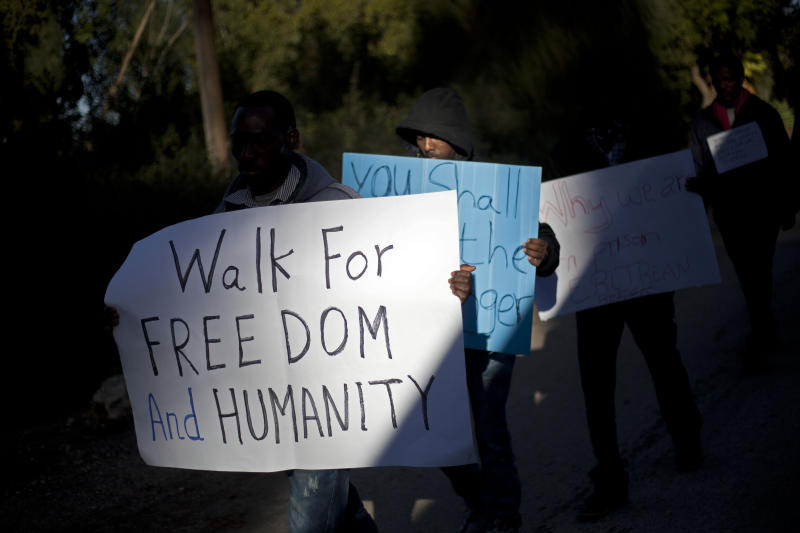 African migrants hold signs as they march from kibbutz Nachshon, central Israel, to Jerusalem,Tuesday, Dec. 17, 2013. Chanting slogans and calling for freedom, some 200 African migrants and Israeli activists ended a two-day march with a rally on Tuesday denouncing Israel's policy of detaining those illegally in the country. (AP Photo/Ariel Schalit)