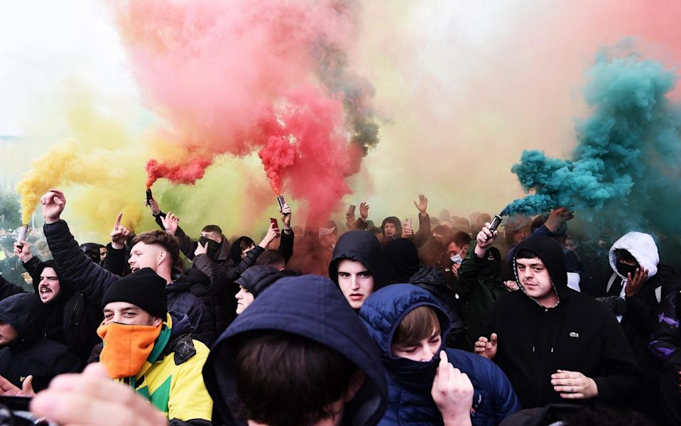 Fans set off smoke flares as they protest outside of Old Trafford on May 13, 2021 in Manchester, England. Police and ground security staff are prepared for a possible demonstration by United supporters against ownership of Manchester United by the Glazer family. - GETTY IMAGES