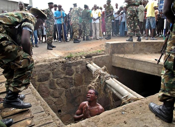 A man begs for help from Burundi's military as he stands in a drain where he had hid to escape a mob lynching in the capital Bujumbura in 2015. (AFP Photo/Aymeric VINCENOT, Aymeric VINCENOT)