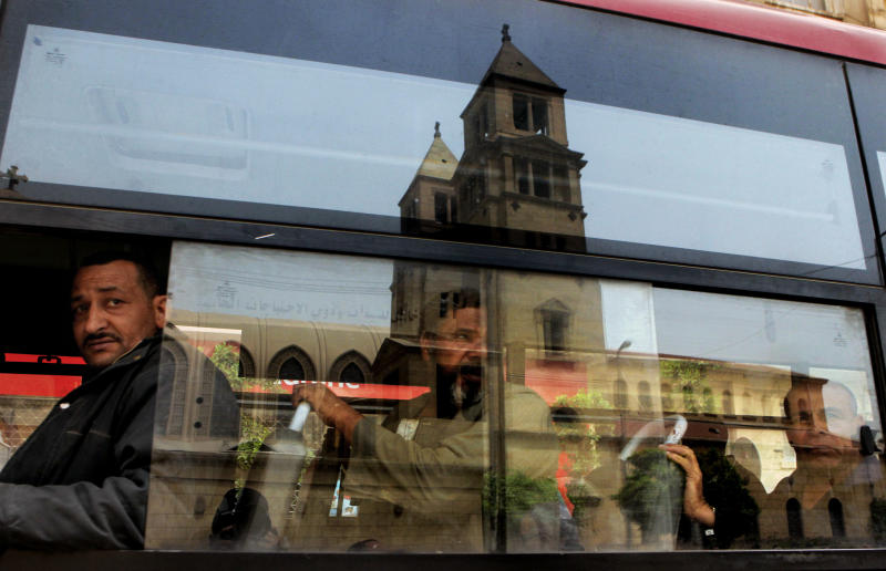 The Coptic cathedral is reflected on the glass of a public bus in Cairo, Egypt, Monday, April 8, 2013. A senior Egyptian health ministry official says the death toll in clashes between Muslims and Christians in Cairo has risen to two. Dozens of people were injured. (AP Photo/Amr Nabil)