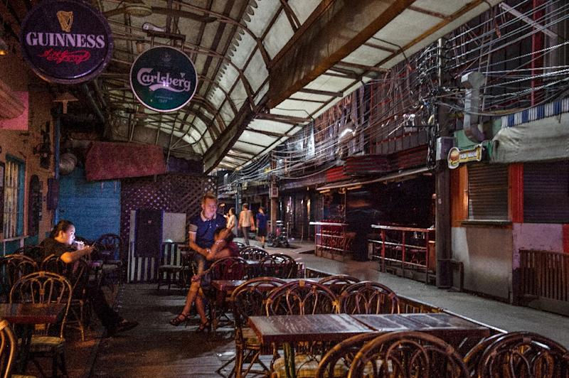 Workers at a bar in Soi Cowboy sit idle on a deserted alley (AFP Photo/Roberto Schmidt)