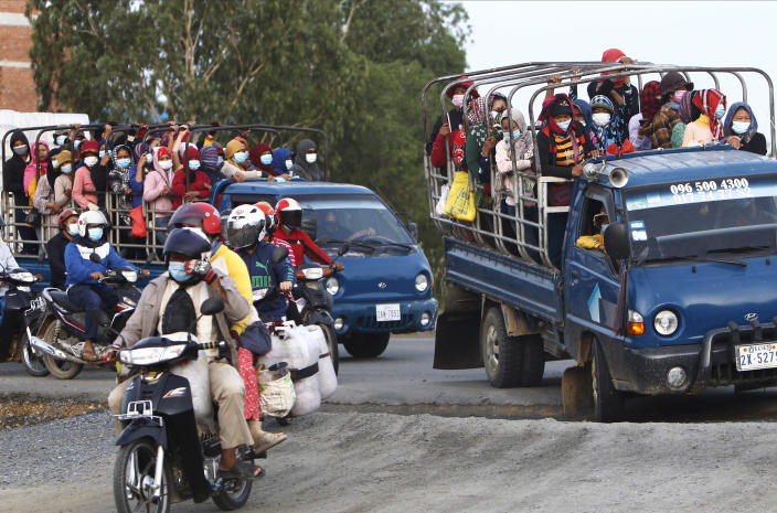 Garment workers stand on the trucks as they head to work outside Phnom Penh, Cambodia, Thursday, May 6, 2021. Cambodia on Thursday ended a lockdown in the capital region. (AP Photo/Heng Sinith)