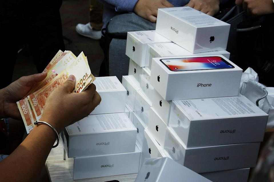 FILE PHOTO: A man pays to buy new iPhone Xs from those who just bought at Apple Stores, on a street in Hong Kong, China November 3, 2017. REUTERS/Bobby Yip