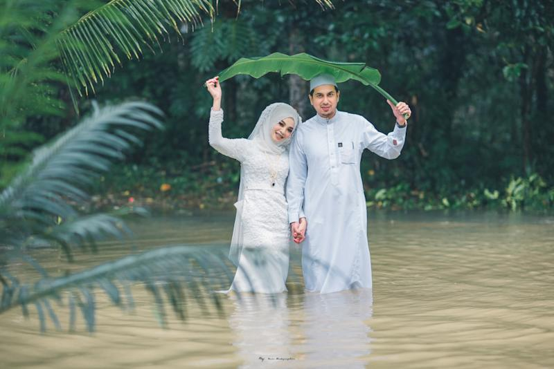 The newlyweds walk in knee-deep floodwater during their wedding photoshoot. — Picture from Facebook/Meen Photographer