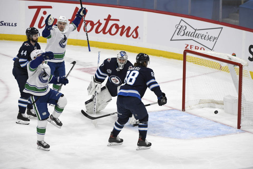 Vancouver Canucks' Nils Hoglander (36) celebrates his goal in front of Winnipeg Jets goaltender Connor Hellebuyck (37) during first period NHL hockey action in Winnipeg, Manitoba on Tuesday March 1, 2021. (Fred Greenslade/The Canadian Press via AP)