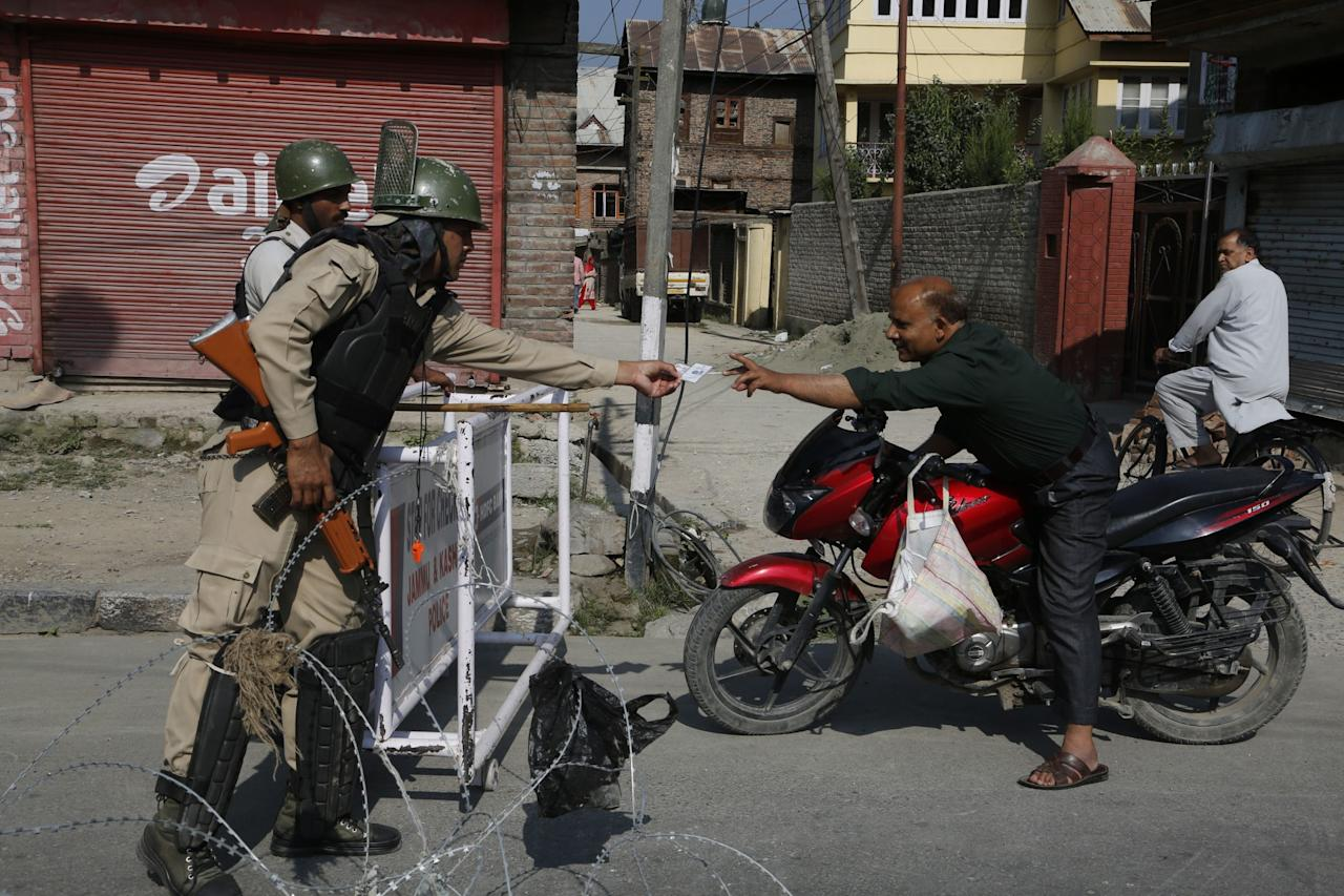 <p>An Indian paramilitary soldier stretches to check the identity card of a Kashmiri man on a motorcycle at a temporary check point during restrictions in Srinagar, Indian controlled Kashmir, Tuesday, July 25, 2017. Kashmiri separatists have called for a strike on Tuesday to protest against the arrest of seven separatist leaders by India's National Investigation Agency on charges of receiving funds from Pakistan-based militant groups. (AP Photo/Mukhtar Khan) </p>