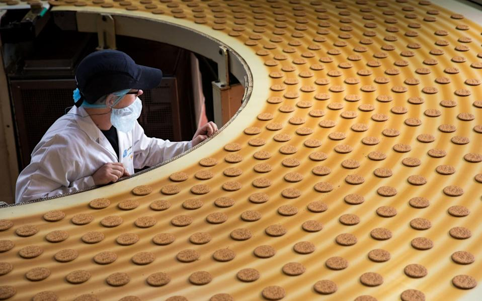 An employee monitors McVitie's Rich Tea biscuits on the production line at United Biscuits factory in London - Jason Alden/Bloomberg
