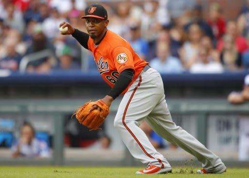 Baltimore Orioles relief pitcher Mychal Givens (60) looks the runner back to third after fielding a ground ball in the seventh inning of a baseball game against the Atlanta Braves, Saturday, June 23, 2018, in Atlanta. The Baltimore Orioles won the game 7-5. (AP Photo/Todd Kirkland)