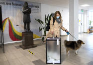 A woman with a dog, wearing face masks to protect against coronavirus, casts her ballot at a polling station during the second round of a parliamentary election in Vilnius, Lithuania, Sunday, Oct. 25, 2020. Polls opened Sunday for the run-off of national election in Lithuania, where the vote is expected to bring about a change of government following the first round, held on Oct. 11, which gave the three opposition, center-right parties a combined lead. (AP Photo/Mindaugas Kulbis)