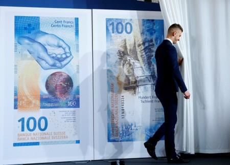 An employee of the Swiss National Bank unveils the new 100 franc banknote during a news conference in Bern
