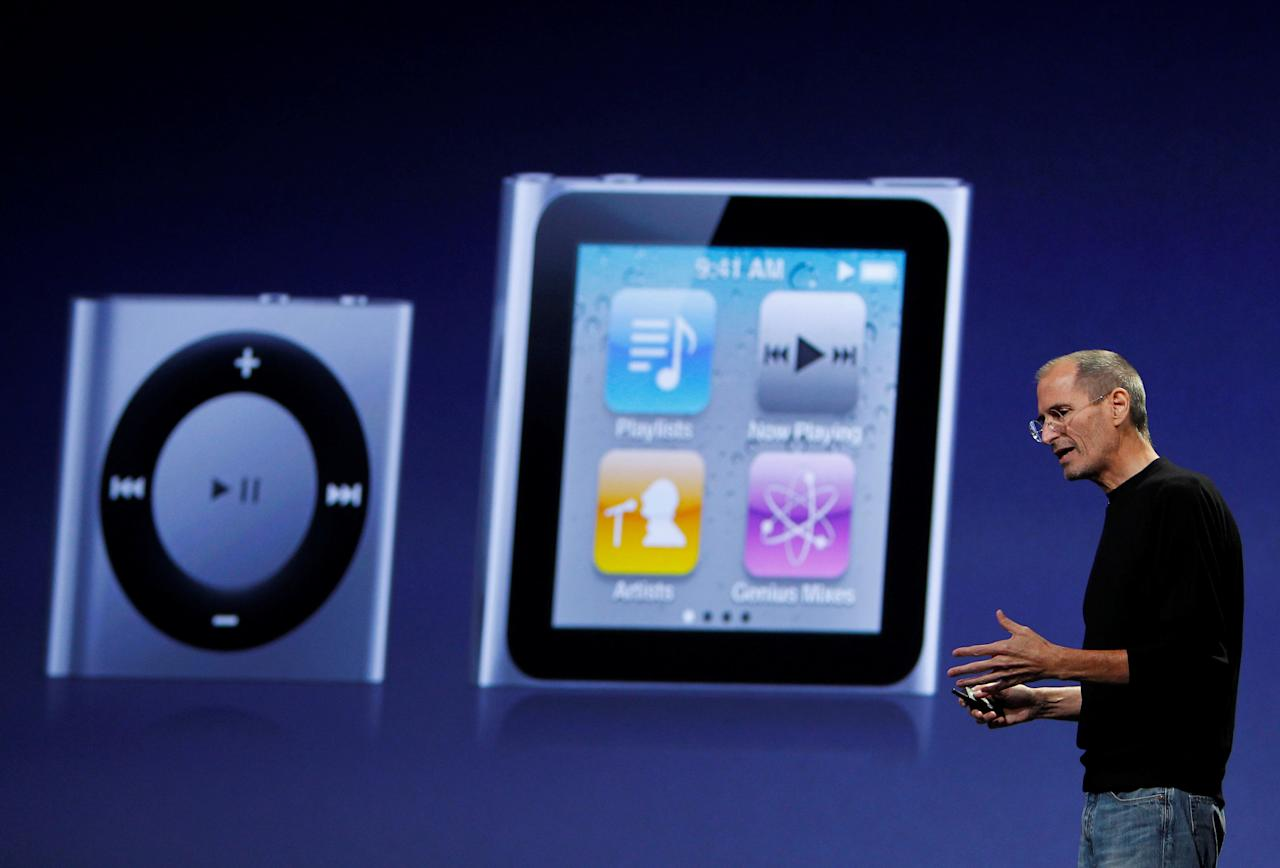 FILE PHOTO: Apple Chief Executive Steve Jobs speaks on stage with images of the iPod Shuffle (L) and iPod Nano projected on screen at Apple's music-themed September media event in San Francisco, California September 1, 2010. REUTERS/Robert Galbraith/File Photo