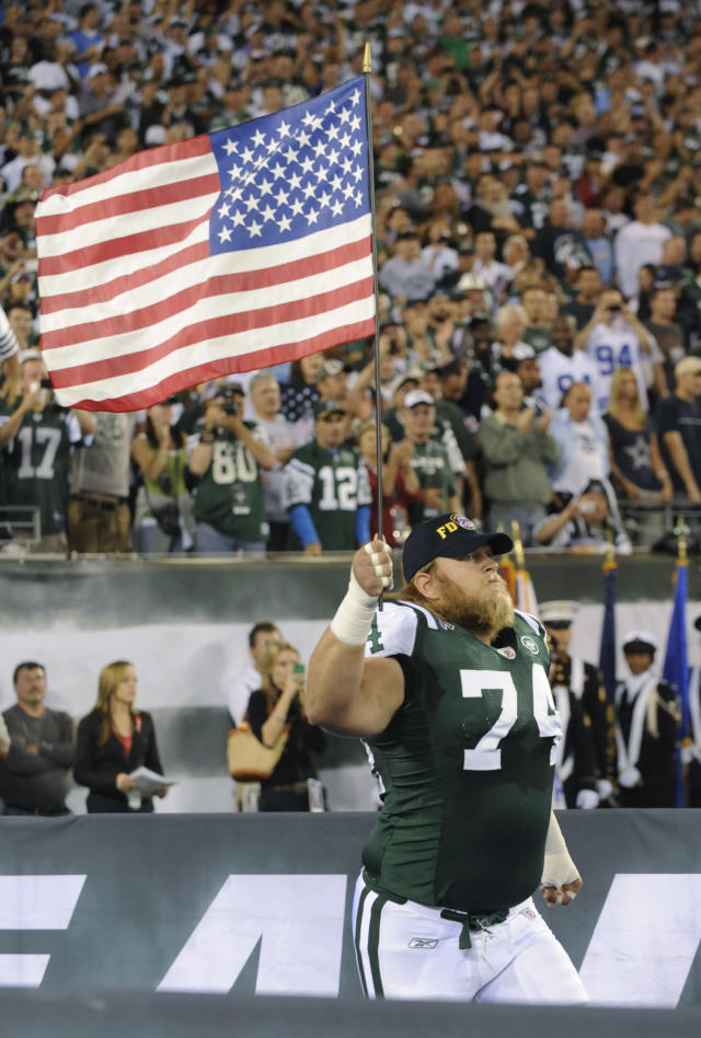 FILE - In this Sept. 11, 2011, file photo, New York Jets center Nick Mangold carries an American flag as he runs on to the field before an NFL football game between the Dallas Cowboys and the Jets, in East Rutherford, N.J. Former New York Jets center Nick Mangold has announced his retirement from playing football after 11 seasons in which he established himself as one of the NFL's best at his position. The 34-year-old Mangold announced on Twitter on Tuesday morning, April 17, 2018, that he will sign a one-day contract with the Jets to retire as a member of the team.(AP Photo/Bill Kostroun, File)