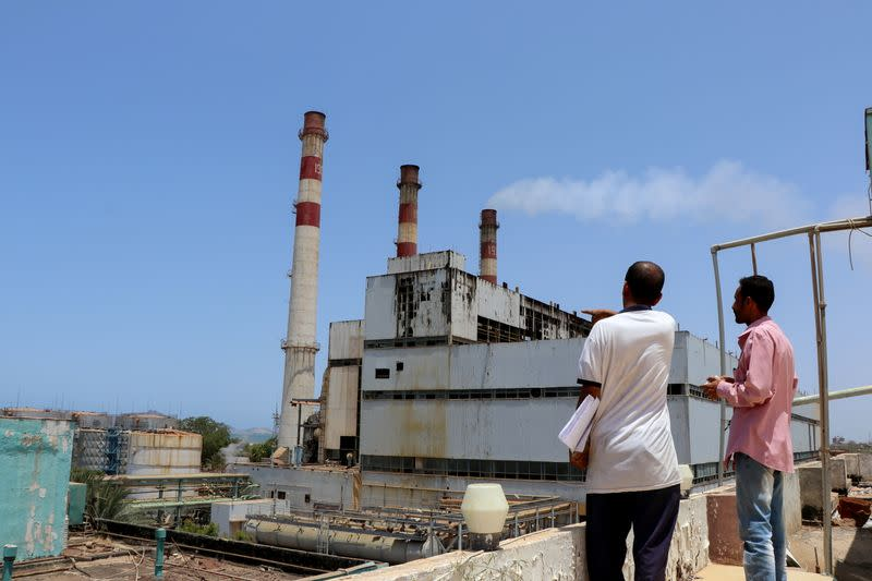 Workers stand at the yard of the state-owned al-Haswa power station in Aden
