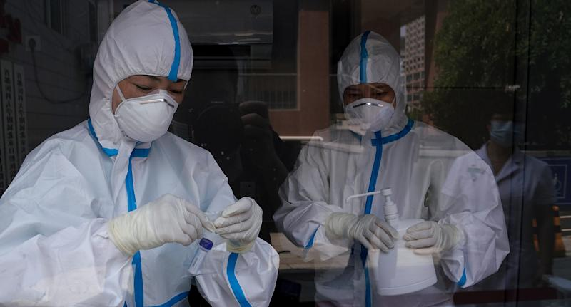 Pictured are medical workers checking test samples at Beijing Puren hospital.