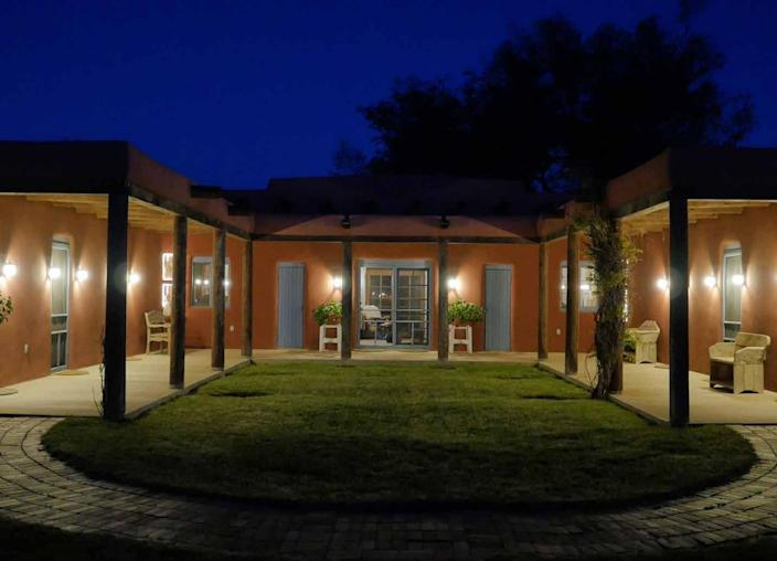 """<p>The Pueblo Revival guest house, dubbed the Hacienda, was designed in 1960 by John Gaw Meem for oilman Buddy Fogelson and his wife, Greer Garson. It's centered on a courtyard.<i> <i>(Photo: <a href=""""http://bit.ly/1oZ16Zz"""" rel=""""nofollow noopener"""" target=""""_blank"""" data-ylk=""""slk:Swan Land Company"""" class=""""link rapid-noclick-resp"""">Swan Land Company</a>)</i><br></i></p>"""