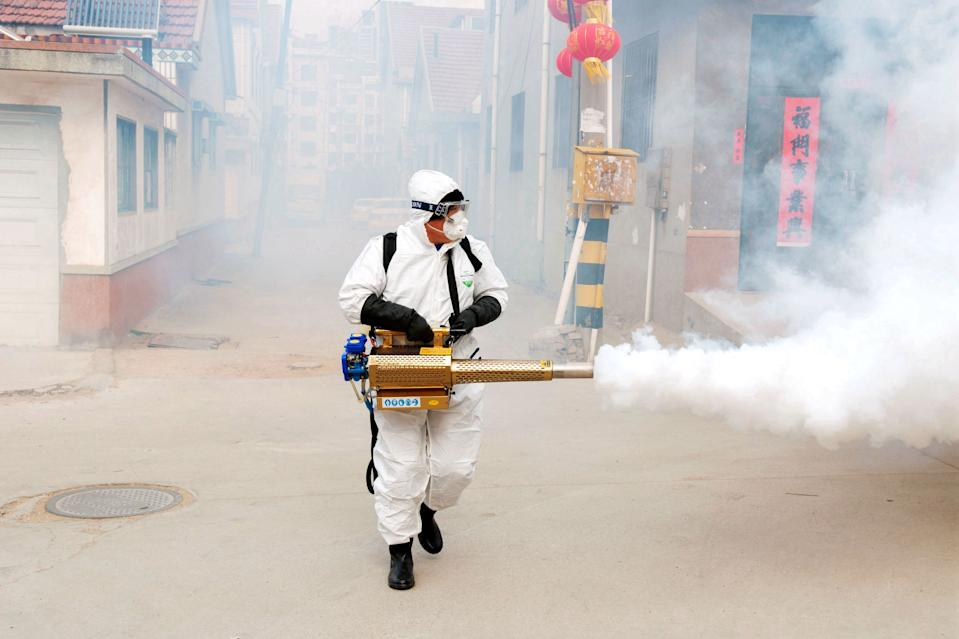 A Chinese volunteer wearing the protective clothing disinfects a street for prevention of the new coronavirus and pneumonia during the Chinese New Year or Spring Festival holiday in Dongxinzhuang Village, Qingdao City, east China's Shandong Province on January 29th, 2020. (Photo by Yu Fangping / Costfoto/Sipa USA)