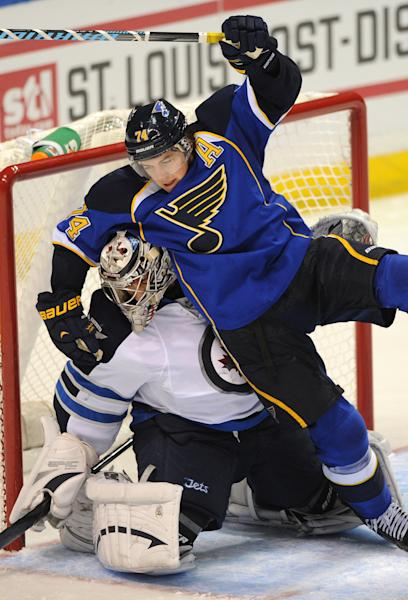 St. Louis Blues' T.J. Oshie (74) falls over Winnipeg Jets' goalie Ondrej Pavelec, left, of the Czech Republic during the third period of an NHL hockey game Tuesday, Oct. 29, 2013, in St. Louis. The Blues won 3-2. (AP Photo/Bill Boyce)