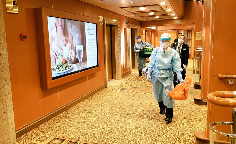 Medical workers in protective suits walk on the cruise ship Diamond Princess anchored off Yokohama, south of Tokyo.