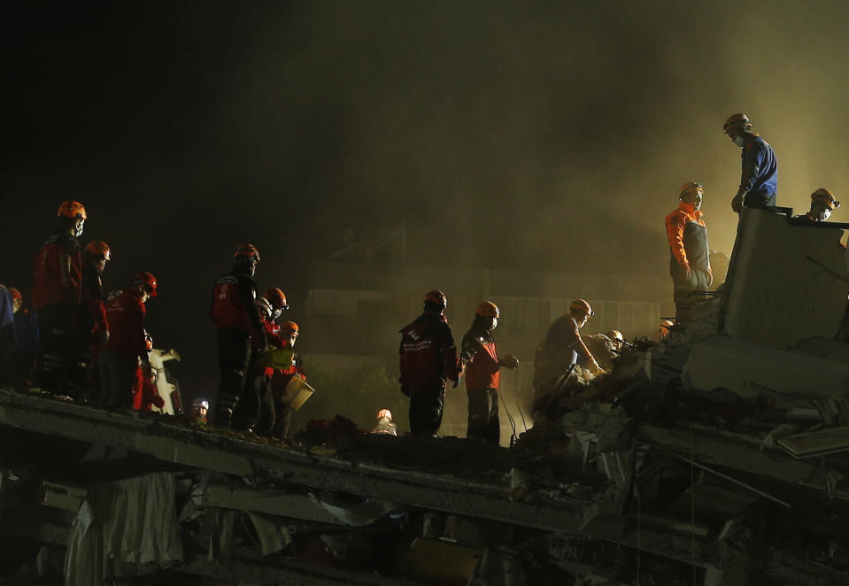 Members of rescue services search for survivors in the debris of a collapsed building in Izmir, Turkey, early Saturday, Oct. 31, 2020. Rescue teams on Saturday ploughed through concrete blocs and debris of eight collapsed buildings in Turkey's third largest city in search of survivors of a powerful earthquake that struck Turkey's Aegean coast and north of the Greek island of Samos, killing dozens. Hundreds of others were injured. (AP Photo/Emrah Gurel)