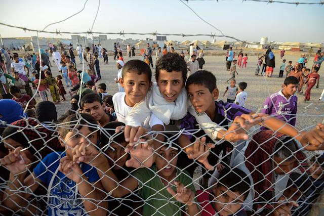 <p>Displaced Iraqi children stand behind a fence at the Hasan Sham camp for Internally Displaced People on June 10, 2017. (Photo: Mohaned El-Shahed/AFP/Getty Images) </p>