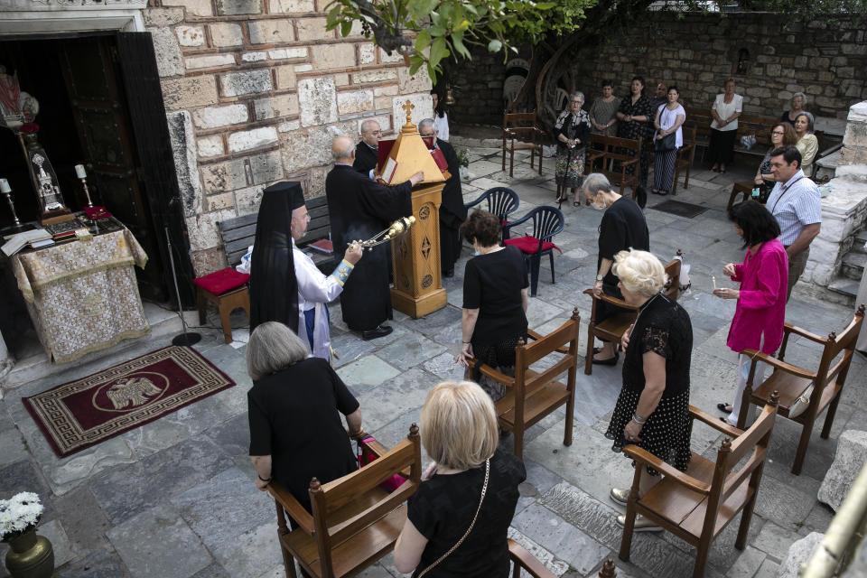 An Orthodox priest swings a chain censer in front of faithful during a Sunday mass taking place outside a church, in Athens, Sunday, May 17, 2020. Greek government allowed churches throughout the country to reopen their doors to faithful on Sunday, a decision that applies to regular services and ceremonies like baptisms and weddings. (AP Photo/Yorgos Karahalis)