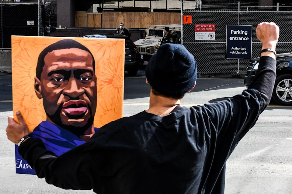 A demonstrator holds a portrait of George Floyd outside the Hennepin County Government Center on March 9, 2021 in Minneapolis, Minnesota.