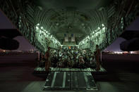 In this image provided by the U.S. Air Force, U.S. Air Force aircrew, assigned to the 816th Expeditionary Airlift Squadron, assist qualified evacuees boarding a U.S. Air Force C-17 Globemaster III aircraft in support of the Afghanistan evacuation at Hamid Karzai International Airport, Kabul, Afghanistan, Saturday, Aug. 21, 2021. (Senior Airman Taylor Crul/U.S. Air Force via AP)