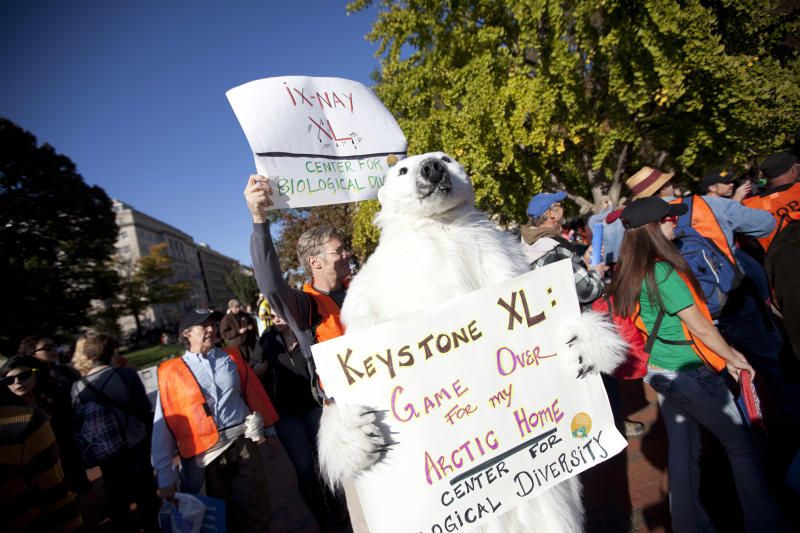 Demonstrators march with a replica of a pipeline during a protest to demand a stop to the Keystone XL tar sands oil pipeline outside the White House on Sunday, Nov. 6, 2011, in Washington.  (AP Photo/Evan Vucci)