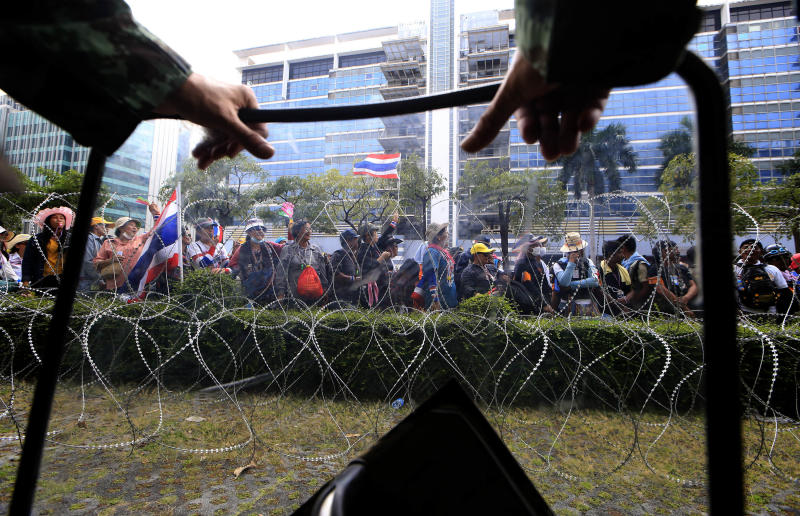 A Thai soldier, foreground, looks at anti-government protesters led by Suthep Thaugsuban stage a rally outside the office of Permanent Secretary for Defense, a temporary office of Prime Minister Yingluck Shinawatra on the outskirts of Bangkok, Thailand Wednesday, Feb. 19, 2014. Anti-government protesters surrounded Yingluck's temporary office in Bangkok's northern outskirts to demand her resignation a day after clashes with police. (AP Photo/Wason Wanichakorn)