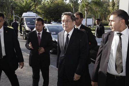 China's Yu, chairman of the CPPCC, is escorted by staff members as he arrives at the Foreign Ministry in Rabat