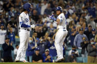 Los Angeles Dodgers' Justin Turner, center, celebrates his solo home run with Cody Bellinger during the seventh inning of a baseball game against the Arizona Diamondbacks Monday, Sept. 13, 2021, in Los Angeles. (AP Photo/Marcio Jose Sanchez)