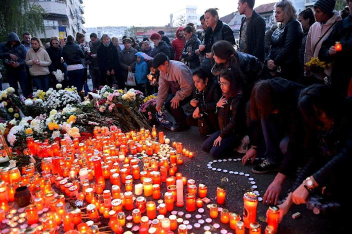 People light candles to commemorate the victims outside the nightclub Colectiv in Bucharest on October 31, 2015 (AFP Photo/Daniel Mihailescu)