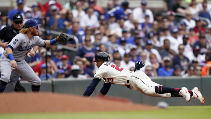 Atlanta Braves' Ehire Adrianza, right,slides into third base ahead of the throw to Los Angeles Dodgers third baseman Justin Turner, front left, after a ground ball by William Contreras in the fourth inning of a baseball game Sunday, June 6, 2021, in Atlanta. (AP Photo/Brynn Anderson)
