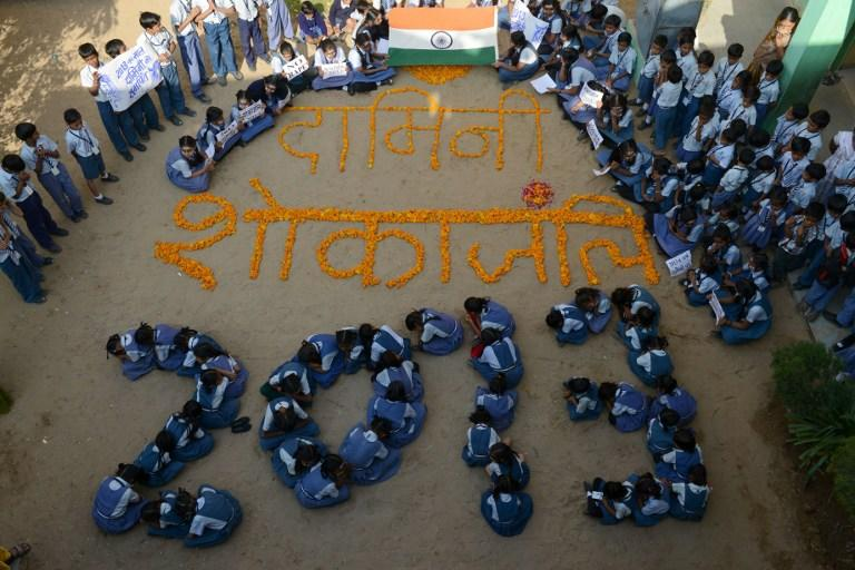 Indian school children pose for a photo as they pay homage to Delhi's rape victim as they welcome 2013 in Ahmedabad on December 31, 2012. Sydney will kick off a wave of dazzling firework displays welcoming in 2013, from Dubai to Moscow and London, with long-isolated Yangon joining the global pyrotechnics for the first time. AFP PHOTO / Sam PANTHAKY
