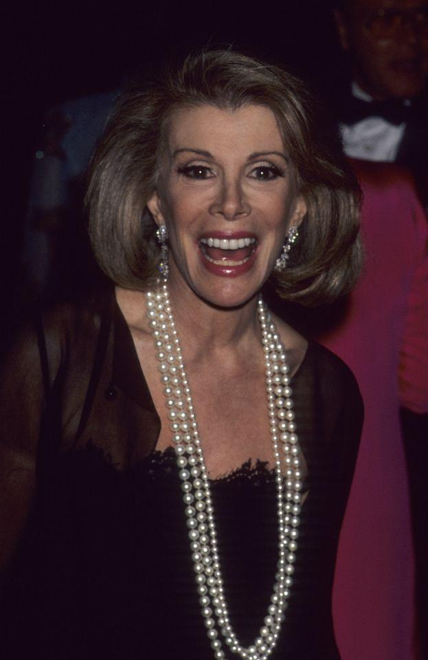 "<p>Before she was a red carpet commentator, comedian <a rel=""nofollow"" href=""https://www.yahoo.com/beauty/muppets-take-manhattan-has-been-one-of-my-96648187813.html"">Joan Rivers</a> was hosting <em>The Joan Rivers Show</em> until 1993. At the Met Gala in 1992, the red-carpet queen donned flashy diamond earrings and long pearl strands with her glossy red lips. </p>"