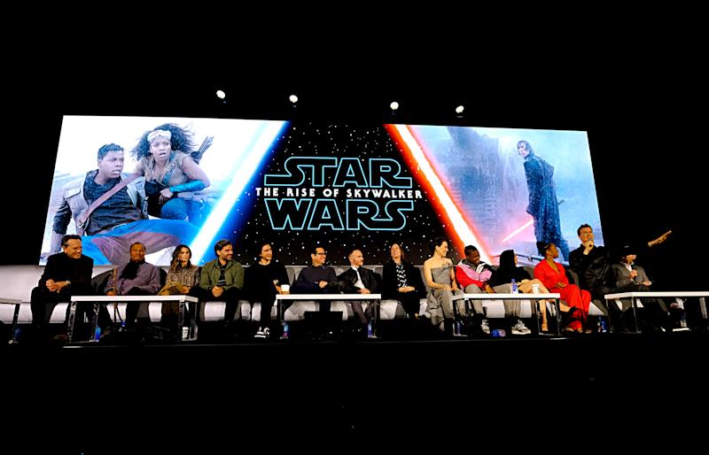 "PASADENA, CALIFORNIA - DECEMBER 04: (L-R) Richard E. Grant, Billy Dee Williams, Keri Russell, Oscar Isaac, Adam Driver, Writer/director J.J. Abrams, Co-writer Chris Terrio, Producer and President of Lucasfilm Kathleen Kennedy, Daisy Ridley, John Boyega, Kelly Marie Tran, Naomi Ackie, Joonas Suotamo and Anthony Daniels participate in the global press conference for ""Star Wars: The Rise of Skywalker"" at the Pasadena Convention Center on December 04, 2019 in Pasadena, California. (Photo by Alberto E. Rodriguez/Getty Images for Disney)"