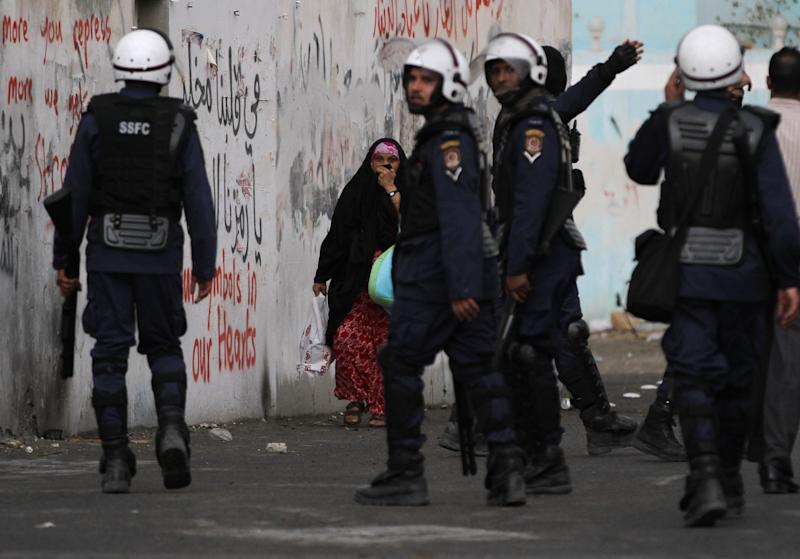 A woman passes a wall covered in layers of anti-government graffiti while riot police pursue Bahraini anti-government protesters in the village of Diraz, Bahrain, on Thursday, April 18, 2013. Organizers of Bahrain's Formula One Grand Prix, to be held Sunday, said Thursday that sporadic protests against the race and violent unrest across the Gulf nation do not pose a threat to the premier international event in the kingdom. (AP Photo/Hasan Jamali)