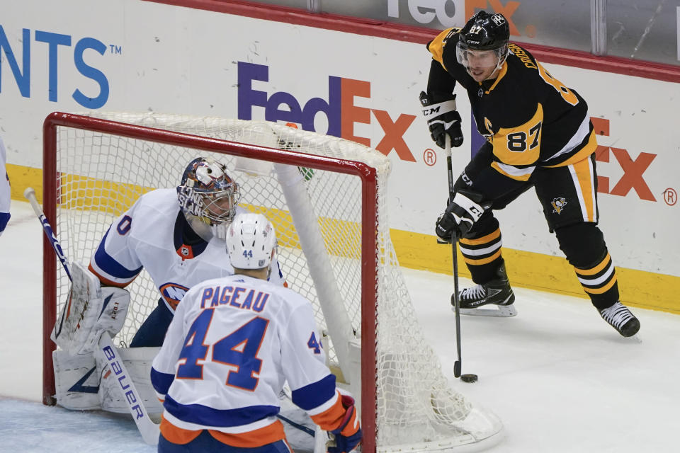 Pittsburgh Penguins' Sidney Crosby (87) looks to pass from behind New York Islanders goaltender Semyon Varlamov (40) as Islanders' Jean-Gabriel Pageau (44) defends during the third period of an NHL hockey game, Saturday, Feb. 20, 2021, in Pittsburgh. (AP Photo/Keith Srakocic)