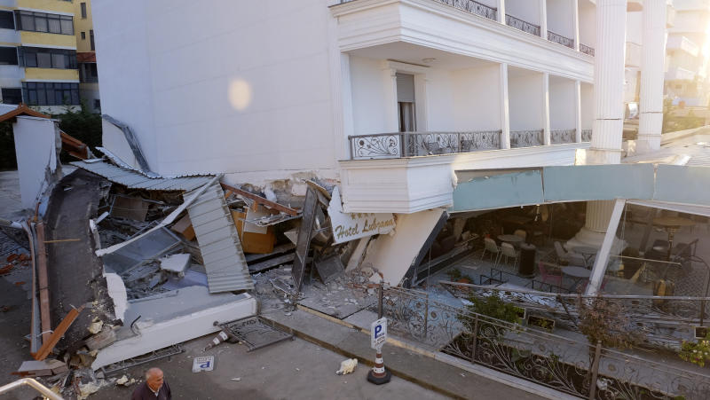 A man passes next to a damaged building after a magnitude 6.4 earthquake in Durres, western Albania, Tuesday, Nov. 26, 2019. (Photo: Hektor Pustina/AP)