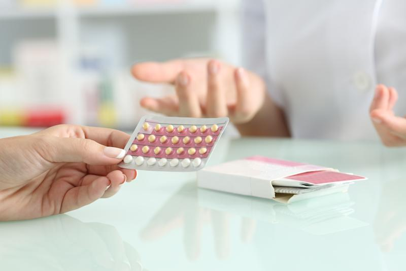 Close up of a girl hands buying contraceptive pills and pharmacist explaining in a pharmacy