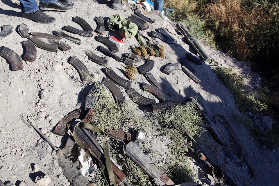 In this photo released by the Syrian official news agency SANA, weapons and ammunition are seen on the ground which were carried by Syrian rebels after they were killed by Syrian government forces, according to SANA, near the Otaiba area, near Damascus, Syria, Friday, Oct. 25, 2013. Syrian government troops on Friday ambushed rebels near the capital, Damascus, killing at least 40 opposition fighters, state media reported. The ambush was part of the military's offensive against rebel strongholds around President Bashar Assad's seat of power. (AP Photo/SANA)