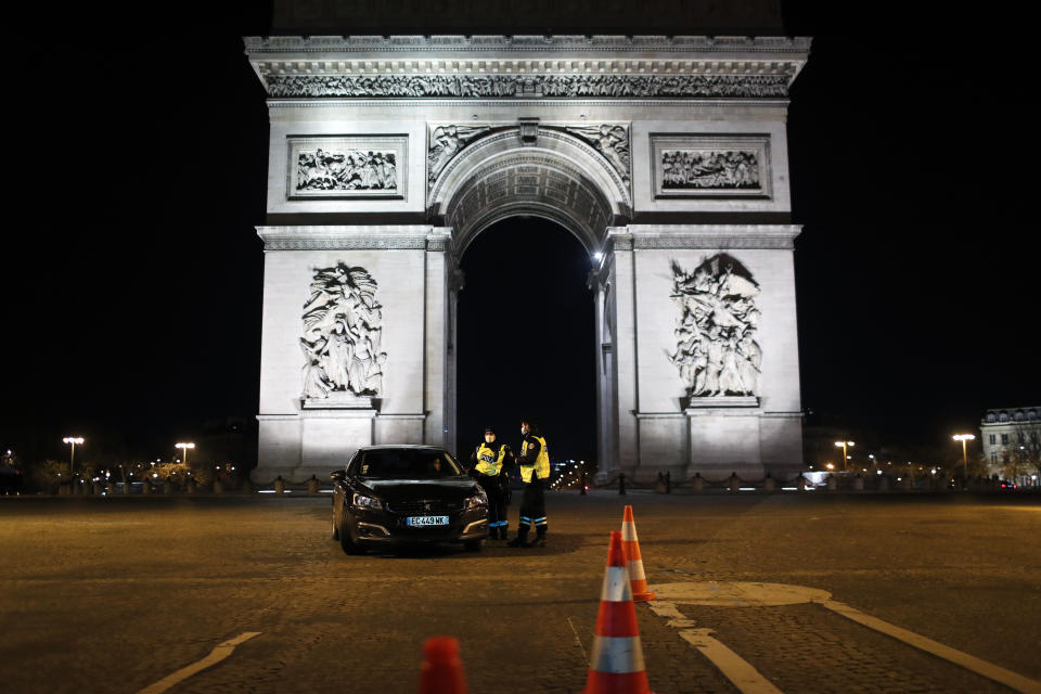 Police officers controls a car on the Champs Elysees avenue next to the Arc of Triomphe during the New Year's Eve, in Paris, Thursday, Dec. 31, 2020. As the world says goodbye to 2020, there will be countdowns and live performances, but no massed jubilant crowds in traditional gathering spots like the Champs Elysees in Paris and New York City's Times Square this New Year's Eve. (AP Photo/Thibault Camus)