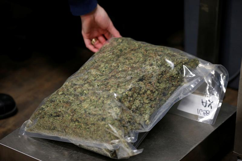 A worker weighs a package of dried marijuana at the Canopy Growth Corporation facility in Smiths Falls, Ontario, Canada, January 4, 2018. Picture taken January 4, 2018. To match Insight CANADA-MARIJUANA/INNOVATION REUTERS/Chris Wattie