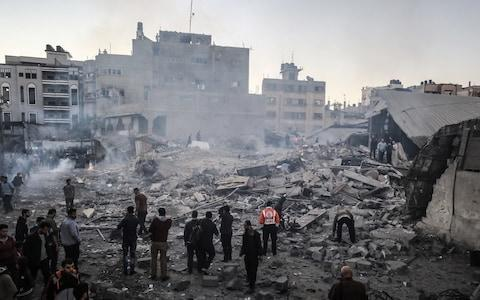 <span>Palestinians gather at the site devastated after an Israeli airstrike hit a five-storey building in the Gaza Strip in response to rockets said were fired towards the country</span> <span>Credit: Analdolu </span>