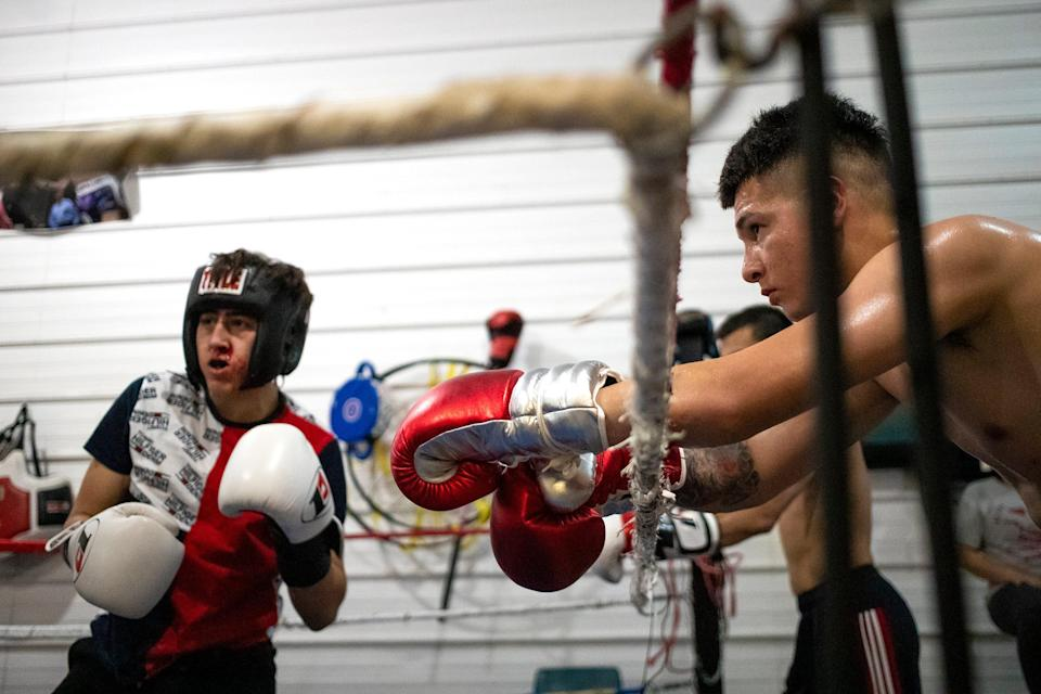 Armani Hill, 20, right, rest his arms on the ropes as he watches Manuel Lomeli, 17, grapple during practice at Soaring Eagles Boxing Club, Tuesday, Aug. 10, 2021, in Green Bay, Wis. Samantha Madar/USA TODAY NETWORK-Wisconsin