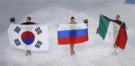 Russia's Adelina Sotnikova (C), Korea's Yuna Kim (L) and Italy's Carolina Kostner celebrate with their flags after the flower ceremony during the Figure Skating Women's free skating Program at the Sochi 2014 Winter Olympics, February 20, 2014. REUTERS/Issei Kato