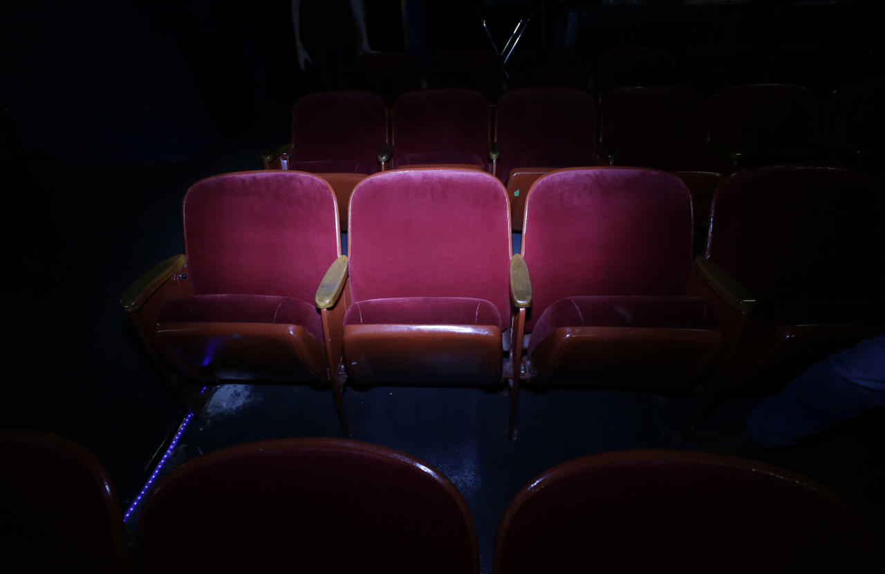 In this photo made Thursday, Oct. 31, 2013, the seat that Lee Harvey Oswald was sitting in when Dallas Police arrested him is illuminated at the Texas Theatre in the Oak Cliff section of Dallas. Oswald was arrested here on Nov. 22, 1963, after the assassination of President John F. Kennedy. (AP Photo/LM Otero)