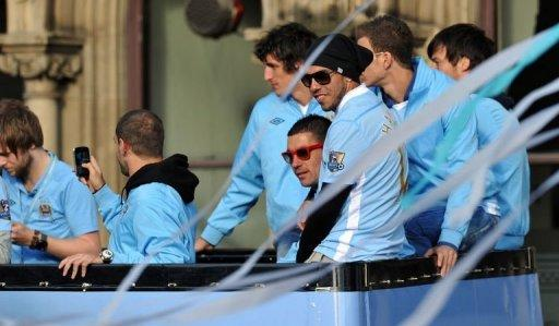 Manchester City's Argentinian forward Carlos Tevez (C, black hat) sits with his teammates on an open topped bus as they celebrate becoming English Premier League champions in a parade in Manchester. Tevez landed himself in fresh controversy on Monday when he was pictured waving a mocked-up tombstone for Sir Alex Ferguson during Manchester City's Premier League title celebrations